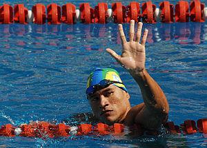 Nadador, usando touca e com óculos de natação colocados na testa, acena para o público de dentro da piscina após uma prova.