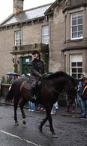 Riding coat - Woman wearing a traditional riding mac at a parade in Coldstream