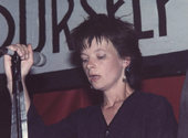 Woman in punk haircut holding microphone on stand