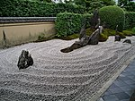 Rock garden with raked gravel and large standing stones in front of a small wall and green plants.