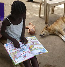 A girl, reading intently. A dog and a doll lie on the ground behind her.