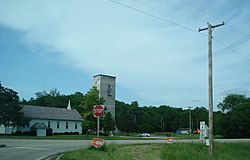 From the right turn lane on Taylor Road, the Bethel Bible Church at left, a rectangular grain elevator building in the center, and Illinois Route 8 sign on the right.