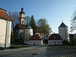 Wehrtürme des Schlosses Groß Laupheim, daneben die katholische Kirche St. Peter und Paul in Laupheim (Baden-Württemberg, Deutschland)