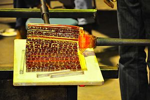Murrine - Picking up a murrina sheet onto a blowpipe while blowing glass.