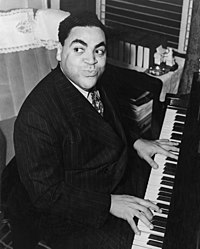 Stocky African-American man sitting and playing the piano. He has black hair and thick black eyebrows, and is grinning and looking to the left. The man is wearing a striped black suit, white shirt and a tie.