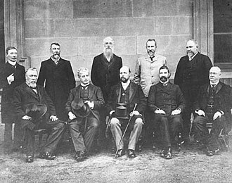 1901 Australian federal election - Edmund Barton is seated second from the left, surrounded by the Federal Executive Council, comprising his Cabinet ministers and the Governor-General, Lord Tennyson. Standing at the rear, left to right are James Drake, Senator Richard O'Connor, Sir Philip Fysh, Charles Kingston, and Sir John Forrest. Seated at the front, left to right are Sir William Lyne, Edmund Barton, Lord Tennyson, Alfred Deakin, and Sir George Turner.