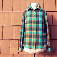 Grenn flannel shirt in front of red brick wall