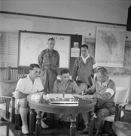 Royal Navy and RAF officers watch as Vice Admiral Kogure appends his signature to the document marking the formal takeover of Seletar airfield from the Japanese, 8 September 1945. Formal takeover of Seletar airfield.jpg
