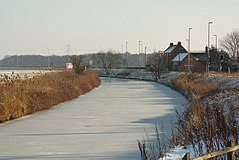 The Fosdyke curves through the picture, its surface smooth white ice. The two banks are brown with dead grass, and the fields either side crop-less and white with hoar. Farther along the bank, in the middle distance, a small group of redbrick buildings are grouped together. Lamp posts are ranged on the right bank, facing away from the canal. They are for lighting the adjacent, but invisible, A57 road.