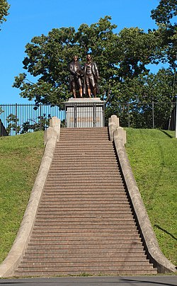 "Photograph showing a long, broad flight of steps leading to a large metal statue of two men. There are about 50 steps. The two men in the statue are roughly life-sized, and are standing on a large stone pedestal. The pedestal has bronze plaque that reads ""Goethe und Schiller""."