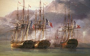 Four ships lie clustered together in shallow water under the shadow of a mountain.