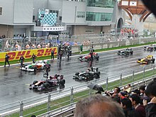 Seven Formula One cars are shown stationary on a wet racing track.