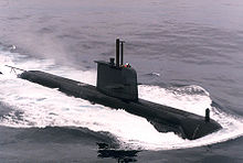 A black submarine travelling on the surface of the sea