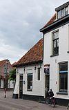 foto van Klein, gepleisterd huisje onder pannen schilddak