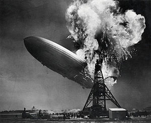 A black and white photograph of an airship near a mooring mast exploding at its stern.