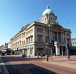 Image shows Hull City Hall. A large 3 story building featuring pillars beneath an arch on one aspect, topped by a copper clad dome