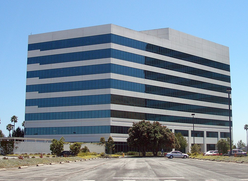 Nondescript eight-story beige building with black windows striped across