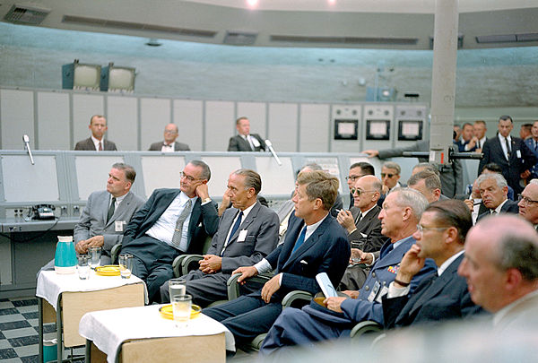 Kurt H. Debus, a former V-2 rocket scientist who became a NASA director, sitting between U.S. President John F. Kennedy and U.S. Vice President Lyndon B. Johnson during a briefing at Blockhouse 34, Cape Canaveral Missile Test Annex. JFK Tour of KSC - GPN-2000-000605.jpg