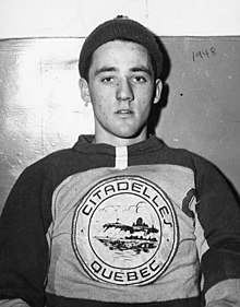 Portrait-photo de Jacques Plante portant un bonnet sur la tête et un maillot de hockey.