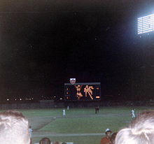 Fans watch a game from the third base line; the scoreboard is visible beyond the right field wall.