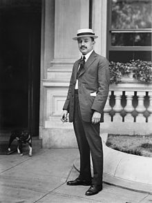 A black and white portrait of a formally dressed young man with a short, black mustache wearing a light-colored hat, white shirt, a light colored suit, dark tie and dark shoes. The man is outside a building where a dog is coming out.