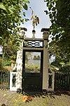 foto van Houten tuinhek met sierlijk houten poortje, bekroond door een beeldje van de faam