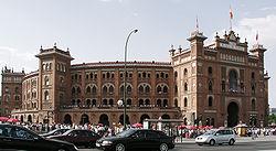 Plaza de Toros Monumental de las Ventas, de estilo neomudéjar, construida (a iniciativa de Joselito) entre 1922 y 1929 por los arquitectos José Espeliú y Manuel Muñoz Monasterio, e inaugurada en 1931. Es la última de una serie de plazas que desde el siglo XVIII fueron «desplazándose», alejándose cada vez más del centro de Madrid por la calle de Alcalá. Los primeros festejos se celebraban en la Plaza Mayor, al igual que los Autos de Fe de la Inquisición, ceremonias religiosas solemnes, coronaciones u otros actos. La primera construida ex profeso, de 1749, estaba junto a la Puerta de Alcalá y el edificio del Pósito. La segunda, a la altura del cruce con la calle Goya, junto a la actual Plaza y monumento de Dalí, en el espacio que ahora ocupa el Palacio de Deportes de la Comunidad de Madrid.