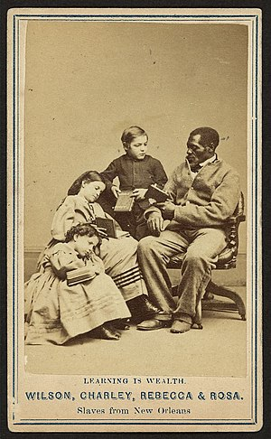 White slave propaganda - Three former slave children with books in their hands alongside a former African American slave