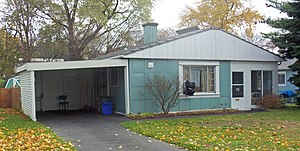A similar blue-green gabled house with grid-pattern metal siding and a carport on the left