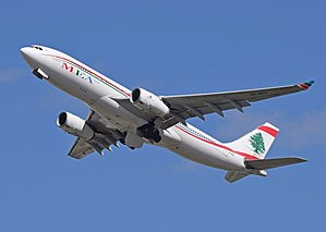 A white, red, blue, and green Middle East Airlines A330 leaving London airport, with the undercarriages still retracting.