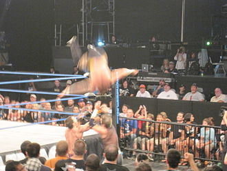 Kid Kash - Kash performing a somersault plancha onto Austin Aries and Jimmy Rave.