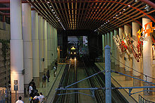 A train enters an enclosed train station with two side platforms. The platforms are decorated with pillars and a piece of artwork.