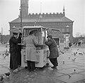 Mensen staan te eten bij een kiosk met op de achtergrond het raadhuis, Bestanddeelnr 252-8832.jpg
