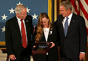 A color image of Murphy's parents standing next to President George Bush in front of an American flag. They are holding Murphy's Medal of Honor in a display case and are looking down at it.