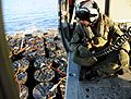 Naval Air Crewman coordinates the pick-up of ammunition during a vertical replenishment. (29032712876).jpg
