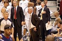 Sloan i dress, omgitt av flere basketballspillere og noen få andre trenere, også i drakter