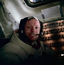 Armstrong smiling in his spacesuit with the helmet off. He wears a headset and his eyes look slightly watery.