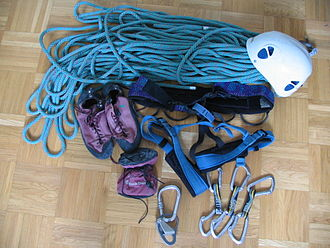 Sport climbing - Sport climbing equipment. From left to right, top to bottom are: rope, helmet, climbing shoes, harness, chalk bag, belay device, and quick draws.