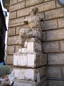 A damaged statue is on a pedestal in front of a stone wall; the pedestal has a number of pieces of paper with writing on them glued to it