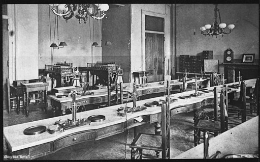 Photograph of the San Francisco Mint Coin Adjusting Room. Tables have assay scales at each station. Coin counting... - NARA - 296577