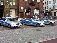 Three patrol cars painted in silver with a blue stripe on the side doors. On the car roof are blue emergency lights.