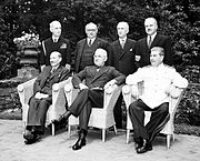 Three men sitting in front and four men standing in the rear, all in suits