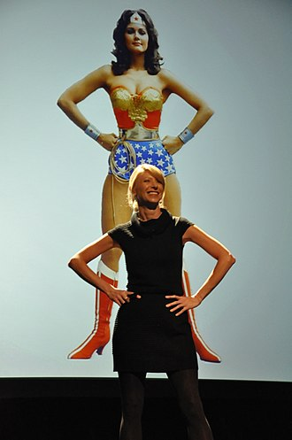 "Power posing - Amy Cuddy demonstrating her theory of ""power posing"" with a photo of the comic-book superhero Wonder Woman"