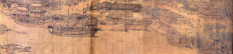 A long, horizontally aligned section of painting that details several large trading barges docked along a river. The barges have curved bottomed hull and vertical wooden walls that are topped in a line of roofing tiles, but do not have actual roofs. Only one of the ships has a mast, although all of the ships do have large rudders.