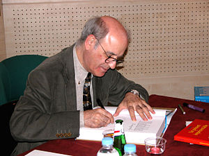 Quino (cartoonist) autographs a book in Paris, 2004.jpg