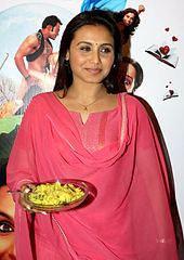 Rani Mukerji is dressed in a pink salwaar and holds a plate of porridge in her hand