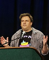 A Caucasian man with average length brown hair wearing an open casual shirt and a t-shirt gestures while making a speech from a podium.