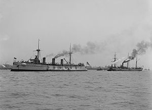 Two warships with steam rising from their smokestacks at anchor off New York harbor