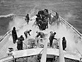 Sailors using steam hoses to clear ice from anchor chains and winches on board HMS SCYLLA during a cold spell on patrol in the Atlantic, February 1943. A15365.jpg