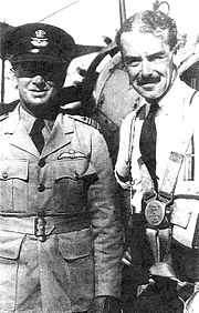 Half-portrait of two men, one wearing light-coloured uniform with dark peaked cap and pilot's wings on left-breast pocket, the other with moustache and wearing civilian clothes and parachute harness
